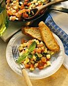 Tomaten-Zucchini-Ragout auf Teller mit Baguettescheiben