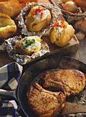 Pork cutlets in pan & baked potatoes on wooden board
