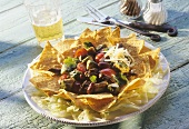 Spicy meat and vegetable salad on tortilla chips