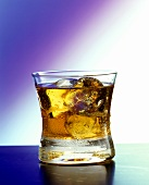 A glass of Rusty Nail with ice cubes