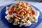 Ham & cheese salad with vegetables on blue glass plate