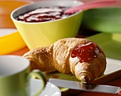 A croissant with red jam