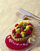 Colourful fruit tartlet on red sauce, on glass plate