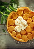 Shortcrust apricot tart with cream & cinnamon on cake rack