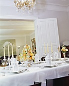 A elegant table laid in white with an arrangement of roses and silver candlesticks