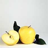 Two Golden Delicious; One Cut in Half