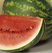 Slice of watermelon in front of whole watermelon