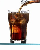 Pouring cola into a glass with ice cubes (glass almost full)