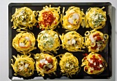 Baked ribbon noodle nests on baking sheet