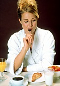Woman at breakfast licking tea spoon