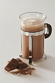 A glass of hot chocolate & two pieces of chocolate