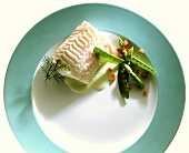 A piece of steamed redfish fillet with mangetouts and dill