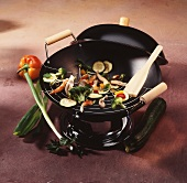 A wok with pieces of vegetables and meat