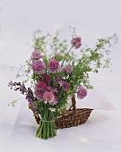 Bunch of flowering herbs in front of wicker basket