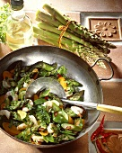 Green asparagus tips with mangetout & chili in wok
