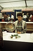 Truffle market in Alba: tradeswoman lifting up glass dome