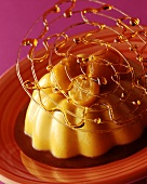 Turned-out crème caramel with caramel spun sugar on plate