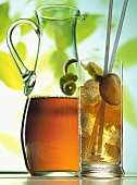 Iced tea in carafe & glass with ice cubes & limes