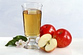 A glass of apple juice, with apples, apple halves & blossom