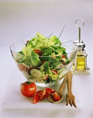 A Large Bowl of Tossed Salad; Salad Servers and Tomatoes