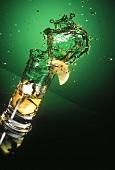 Eistee spritzt aus dem Glas, grüner Hintergrund