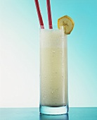 Banana milk shake in glass with straws and slice of banana
