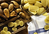 Potatoes in a hand, peeled potatoes & potato slices