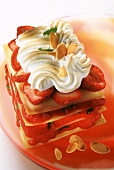 Strawberry lasagna with meringue topping on red glass plate