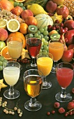 Seven different fruit juices in front of fresh fruit