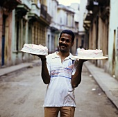 Cuban bakery assistant with two gateaux in the street