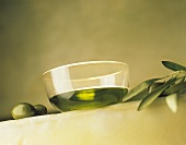 Olive oil in glass bowl, two green olives & olive branch