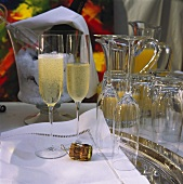 Two filled champagne glasses & empty glasses on buffet table