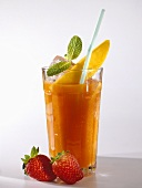 Mango & strawberry drink in glass with straw; strawberries