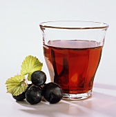 Red grape juice in glass; decoration: red grapes