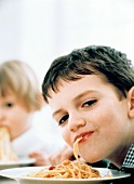 Young boy eating spaghetti, girl in background