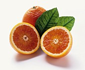 Blood orange: two halves in front of whole orange & leaves