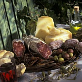 Italian still life with salami, cheese, olives, capers, wine
