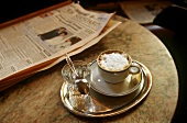 Cup of cappuccino, glass of water & newspaper on café table