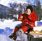Child in winter clothes at table in snow eating bread & cheese