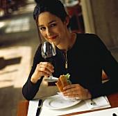Frau isst ein Sandwich & trinkt ein Glas Rotwein im Bistro