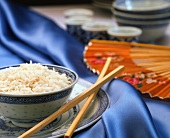 Rice in Asian dish with chopsticks on blue fabric