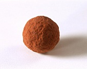 A round chocolate truffle dusted with cocoa