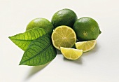 Three limes with leaves, lime half and slice