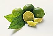 Drei Limetten mit Blättern, Limettenhälfte und -schnitz