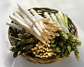 Various types of asparagus in a wicker bowl