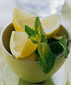 Wedge of lemon and a sprig of lemon balm in bowl