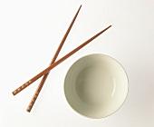Eine Reisschale und zwei rote Stäbchen
