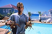 Man Holding Two Langouste Outside of a Resort