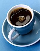 Schwarzer Kaffee in blauer Kaffeetasse auf blauem Untergrund