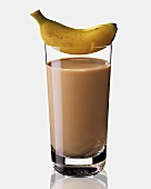 A glass of banana and coffee milk, a baby banana on top